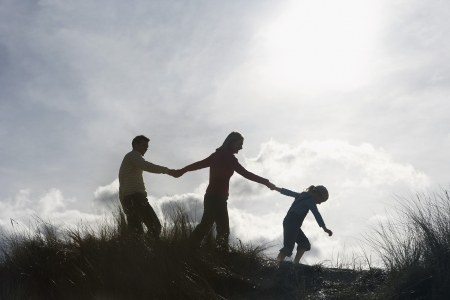 one parent: Silhouette of parents and daughter (5-6) holding hands on sand dunes