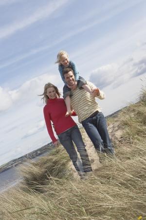 holiday maker: Parents walking with girl (5-6) on fathers shoulders on dunes portrait LANG_EVOIMAGES