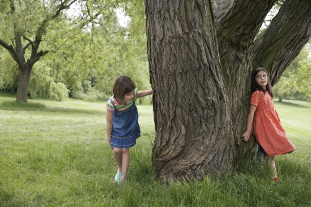 hide and seek: Two girls (7-9) playing hide and seek by tree