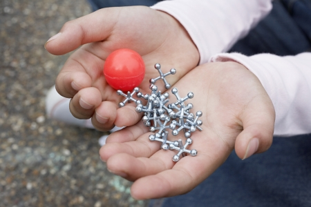 Boy (7-9) holding bouncy ball and jacks close-up Stock Photo - 19547108