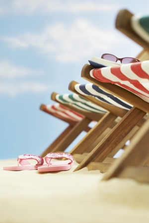 Row of deck chairs on beach focus on flip-flops on ground Stock Photo - 19547119