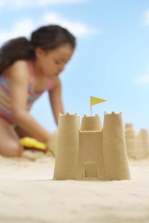 chateau de sable: Fille (7-9 ans) la construction de ch�teaux de sable sur la plage accent sur le ch�teau de sable au premier plan