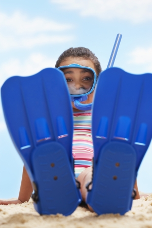 snorkling: Girl (7-9 years) sitting in flippers and snorkling mask on beach