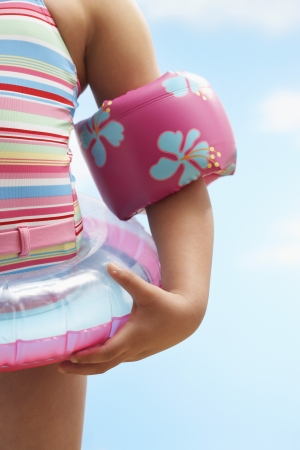 british girl: Girl (7-9 years) wearing inflatable ring and water wings mid section