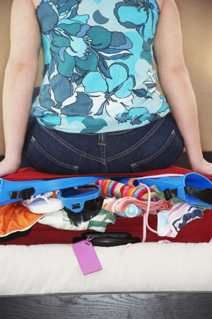 over packed: Mujer sentada en la parte media mullido maleta Vista posterior LANG_EVOIMAGES