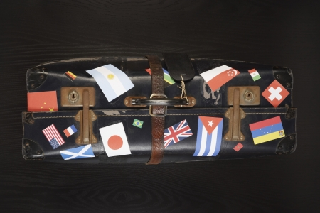 travelled: Suitcase with various flag stickers studio shot