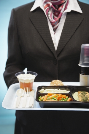 airline uniform: Stewardess holding tray with airplane food mid section