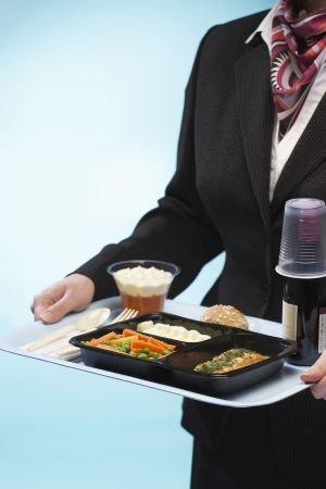 pre adult: Stewardess holding tray with airplane food mid section