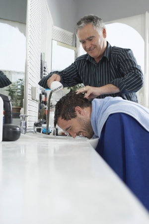 Barber washing mans head in barber shop Stock Photo - 19076154