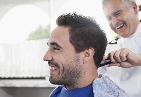 shop skill: Barber cutting mans hair in barber shop close-up
