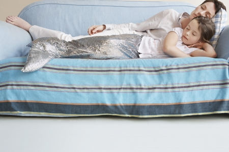 adult mermaid: Young girl (5-6) wearing mermaid costume sleeping on sofa with mother