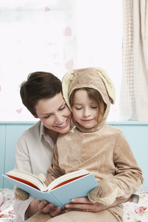 storytime: Mother and daughter (5-6) in bedroom reading book girl in bunny costume LANG_EVOIMAGES