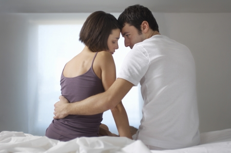 young man short hair: Couple embracing sitting on bed back view LANG_EVOIMAGES