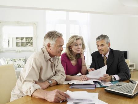 Casal de idosos sentado � mesa com consultor financeiro