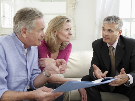 advising: Senior couple sitting on sofa with financial advisor