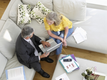 financial advisor: Woman sitting on sofa with financial advisor elevated view