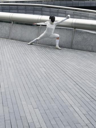fencer: Female fencer lunging, outdoors