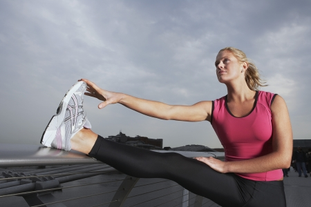 foot bridge: Woman stretching on foot bridge, low angle view LANG_EVOIMAGES