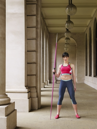 Female athlete holding javelin standing in portico portrait Stock Photo - 19076366