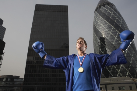 winning location: Boxer wearing gold medal standing in front of downtown skyscrapers low angle view London England LANG_EVOIMAGES
