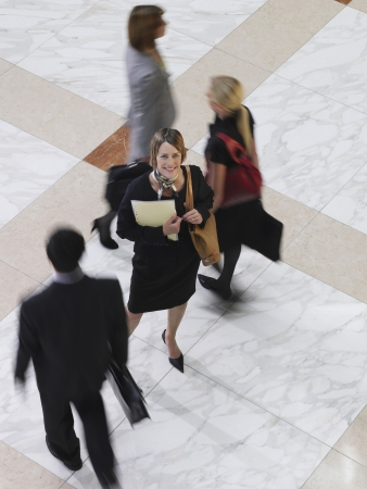 one person with others: Business woman standing amongst people walking elevated view long exposure