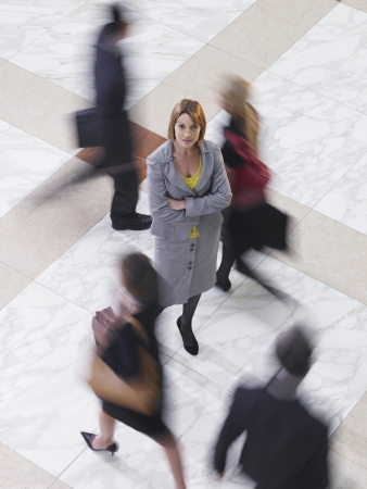 amongst: Business woman standing amongst people walking elevated view long exposure