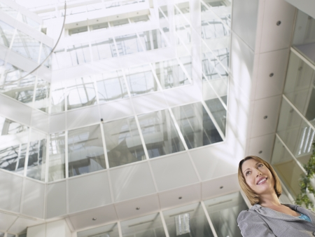view of an atrium in a building: Business woman standing in atrium of office building low angle view