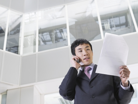 view of an atrium in a building: Business man using mobile phone in atrium of office building low angle view