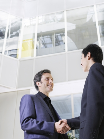 view of an atrium in a building: Two business men shaking hands low angle view
