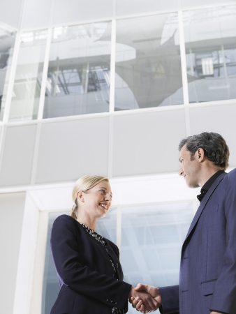 view of an atrium in a building: Two business people shaking hands low angle view side view