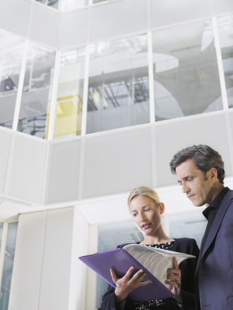 view of an atrium in a building: Two business people looking at paper folder low angle view