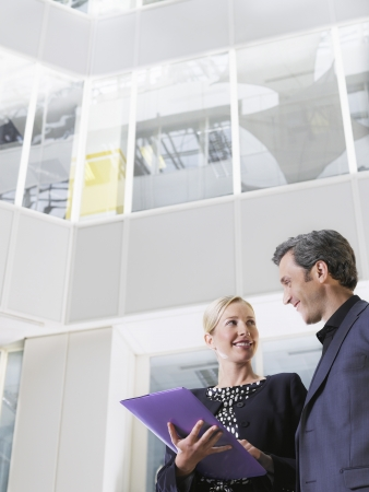 view of an atrium in a building: Two business people smiling holding paper folder low angle view