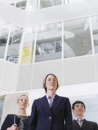 view of an atrium in a building: Three business people standing in atrium of office building low angle view