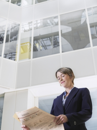 view of an atrium in a building: Business woman reading newspaper in atrium of office building low angle view