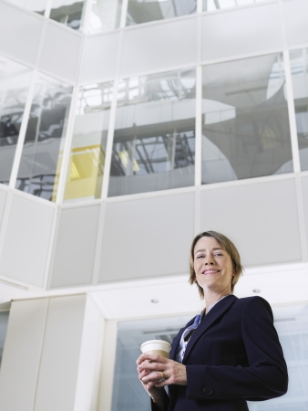 view of an atrium in a building: Business woman holding cup of coffee standing in atrium of office building low angle view LANG_EVOIMAGES