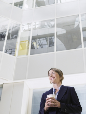 Business woman holding cup of coffee standing in atrium of office building low angle view Stock Photo - 19076424