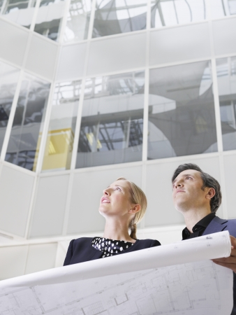 view of an atrium in a building: Two business people holding blueprint low angle view