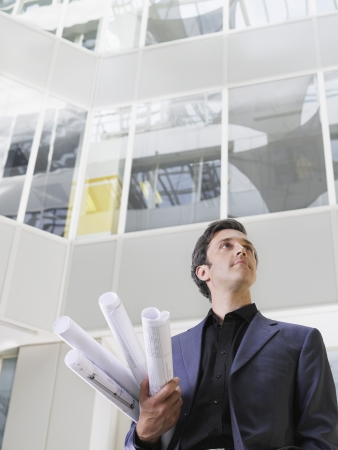 view of an atrium in a building: Business man holding rolled blueprints under arm in atrium of office building low angle view LANG_EVOIMAGES