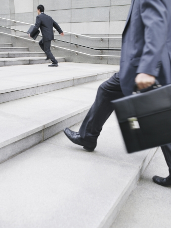 unknown age: Business men hurrying up steps outdoors side view LANG_EVOIMAGES