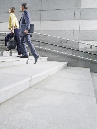 unknown age: Business people walking up steps outdoors side view