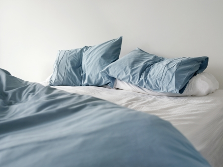 unmade: Morning view of an unmade bed with crumpled blue bed linens and no people