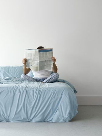 obscured face: Man sitting on bed reading newspaper