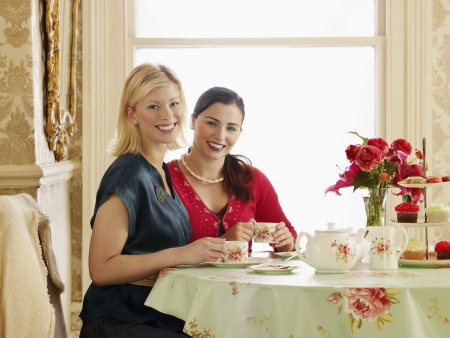 afternoon tea: Two young women sitting at dining table drinking tea portrait