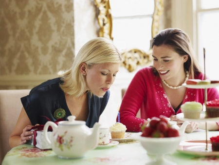 afternoon tea: Two young women sitting at dining table LANG_EVOIMAGES