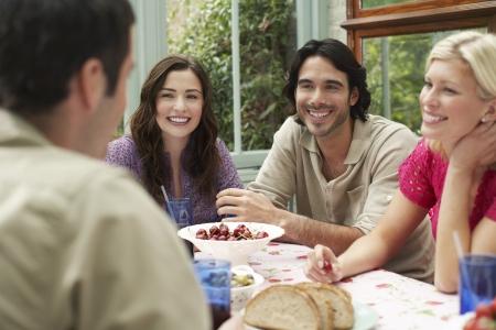 verandah: Group of young people sitting at verandah table laughing