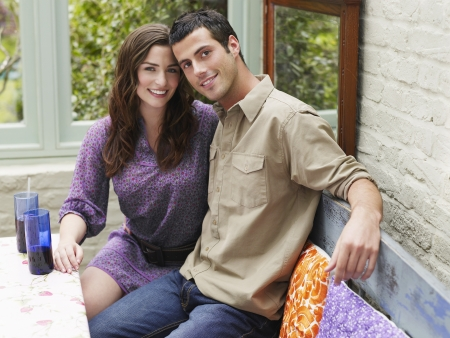 verandah: Young couple sitting at verandah table smiling portrait