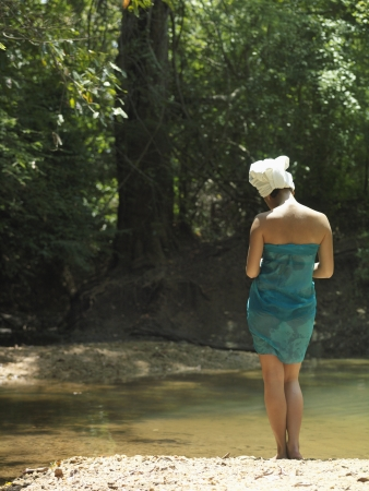 mixed race woman: Young woman lake in forest with towel wrapped on head back view