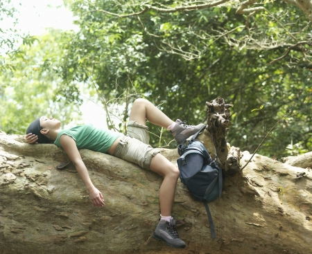 �rock formation�: Young woman resting on rock formation in forest side view LANG_EVOIMAGES