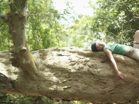 rock formation: Young woman resting on rock formation in forest side view LANG_EVOIMAGES