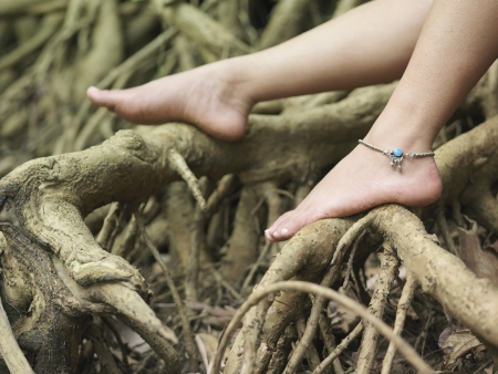 anklet: Young woman sitting on tree roots close-up on foot